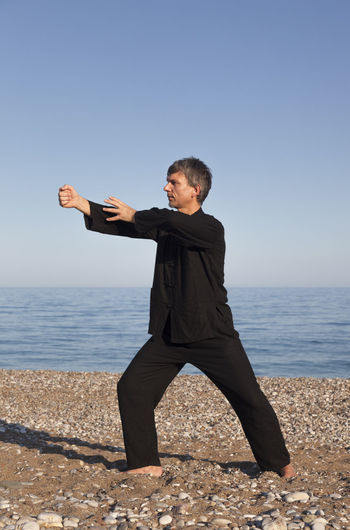 Mature man practicing tai chi at beach against clear blue sky