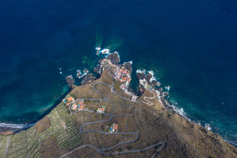 Aerial view at fissured coastline serpentine road and houses at shoreline of canary island