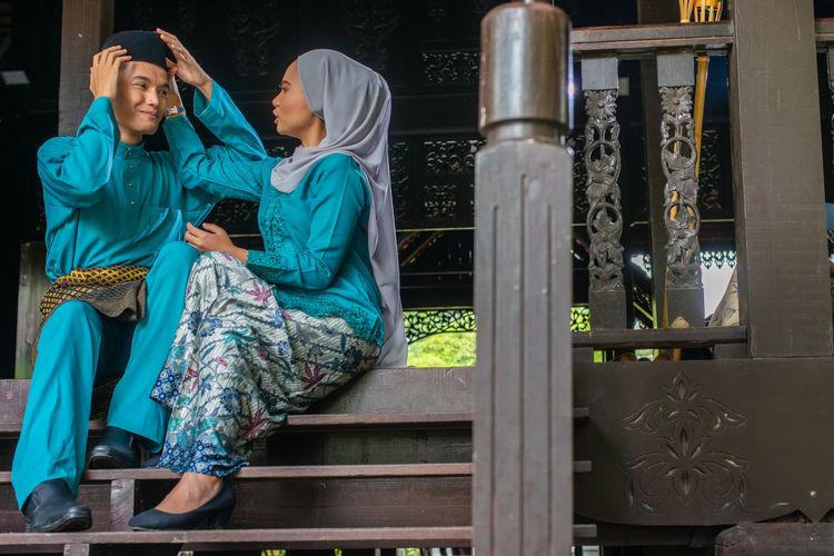 Full length of woman and a man sitting on the stairs of a wooden malay house during eid mubarak.