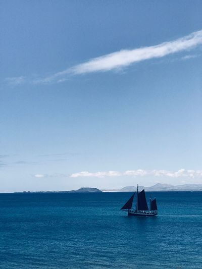 Silhouette Boat On Sea Against Blue Sky