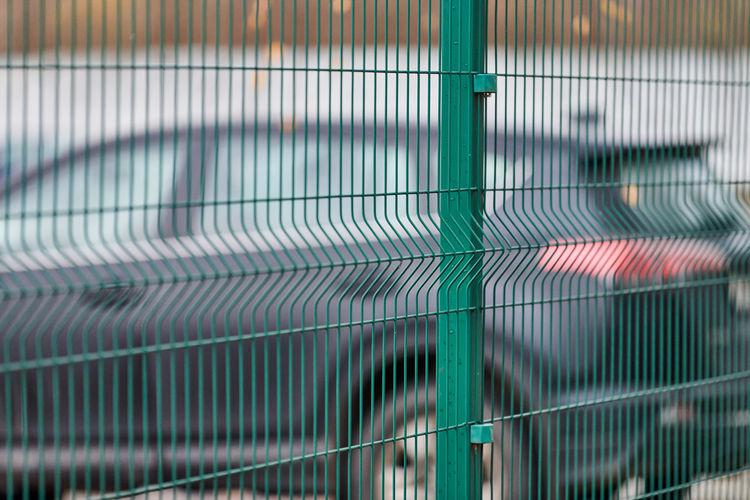 Full frame shot of building seen through metal fence