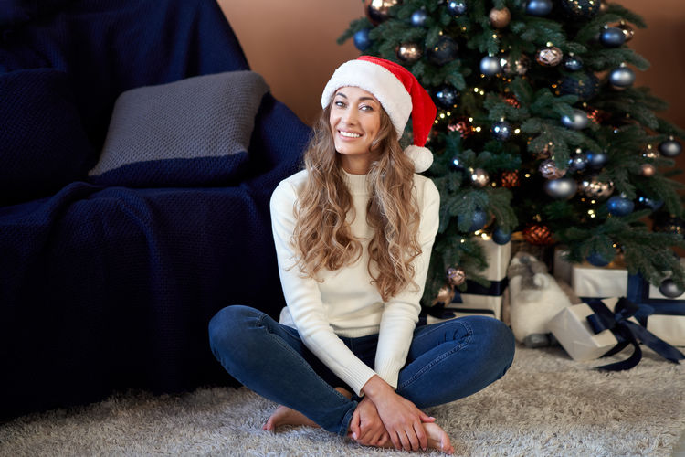 Young woman sitting on christmas tree at home