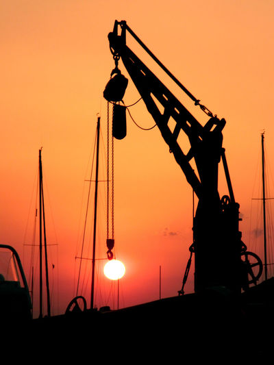 Low angle view of silhouette crane against sky during sunset