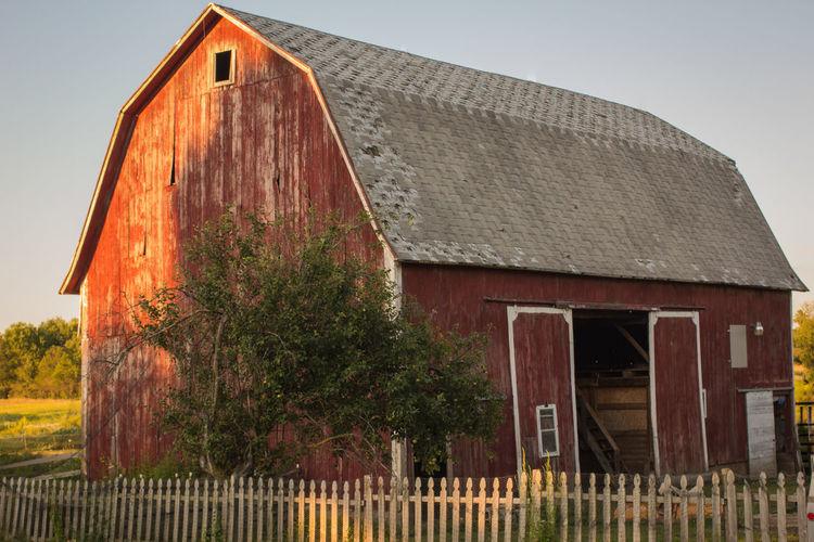 Barn by house against sky