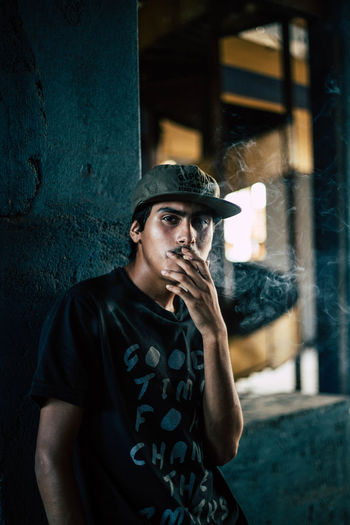 Portrait of young man smoking cigarette against wall