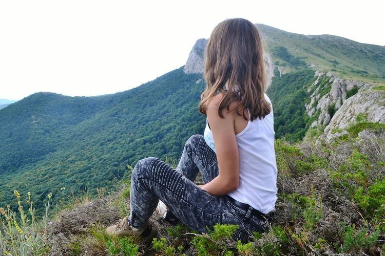Side view of woman sitting on mountain