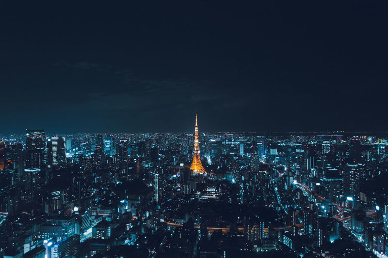 Illuminated tokyo tower amidst buildings against sky at night