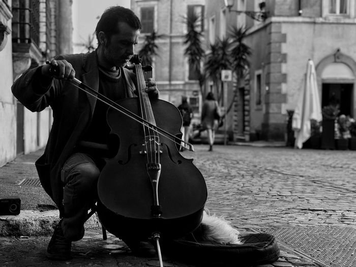 Full length of man playing music in city