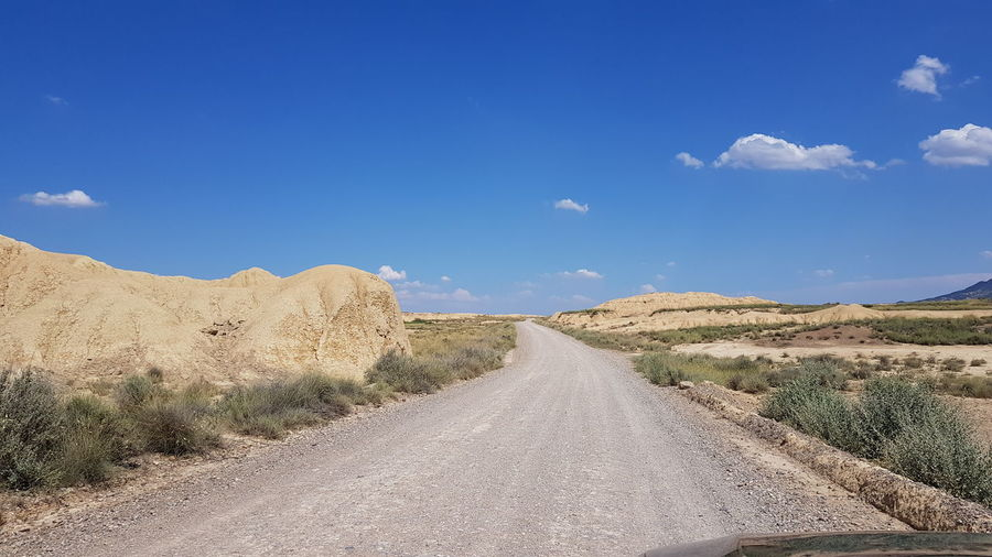 Road amidst land against sky