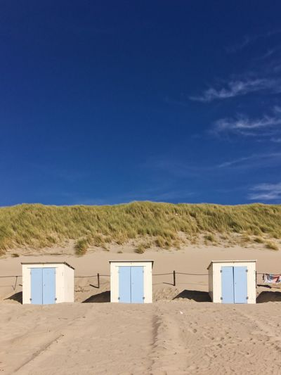 Scenic view of beach cabins against blue sky