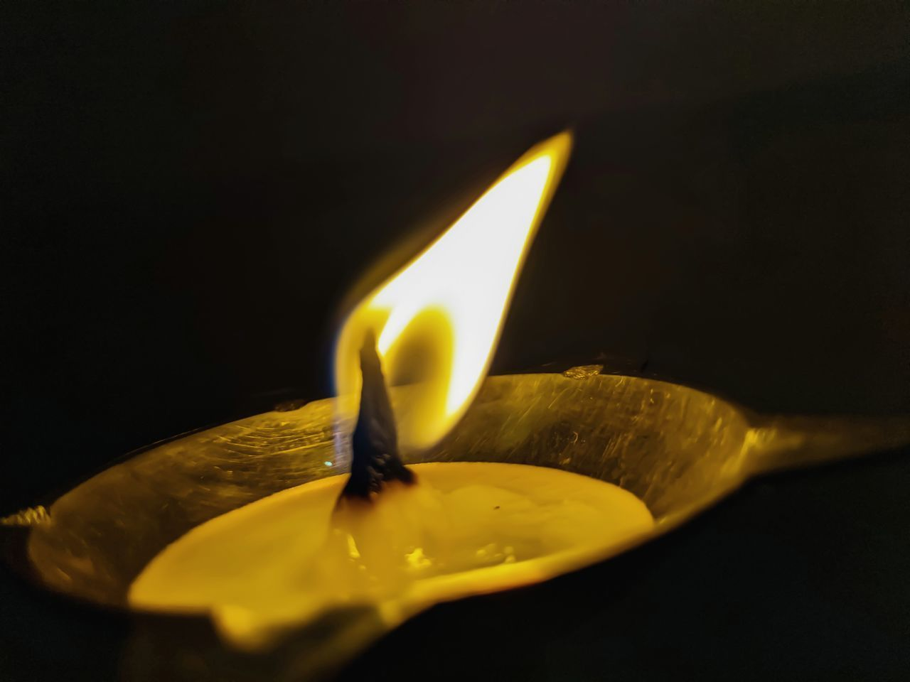CLOSE-UP OF LIT CANDLES IN DARK