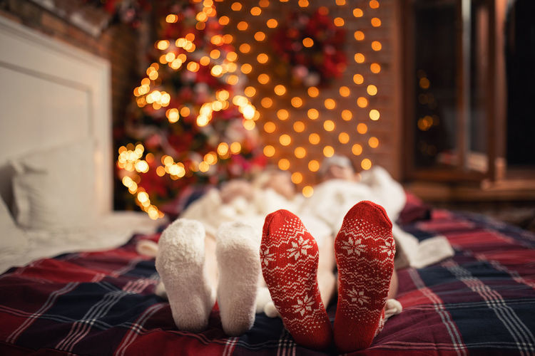 Close-up of christmas decorations at home, people and their christmas socks