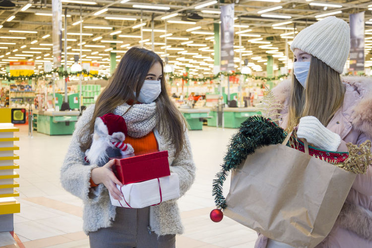 Smiling young women wearing mask holding christmas gifts standing at supermarket
