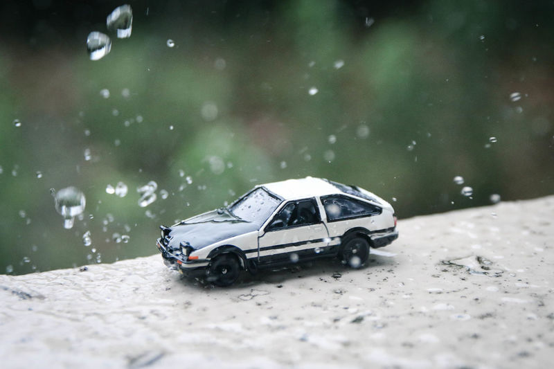 Close-up of toy car on retaining wall during rainy season