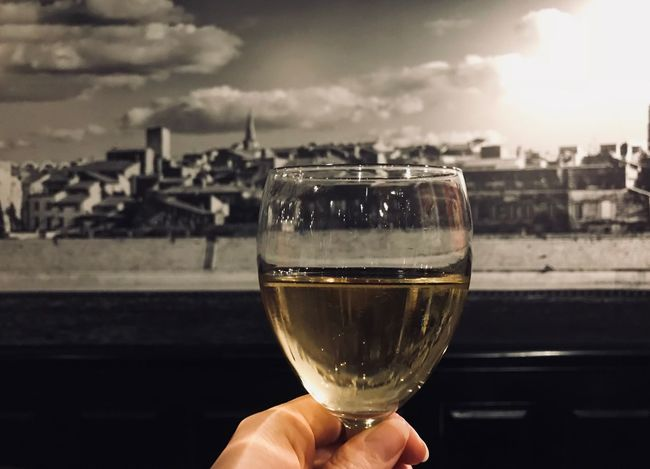 Nightlife France Hello World Myuniquestyle Eye4photography  From My Point Of View Yellow Blackandwhite Tgif Restaurant Cityscape Cheers Wine Moments Wine French Wine Human Body Part Focus On Foreground Human Finger Drink One Person Sky Close-up Drinking Glass Wineglass Alcohol