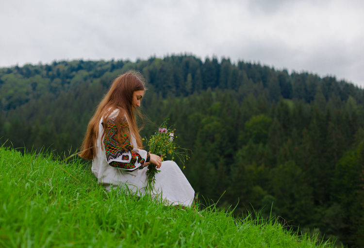 Young woman sitting on field against trees and plants