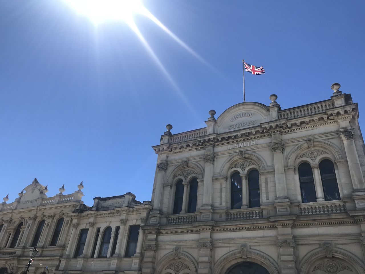 built structure, sky, low angle view, building exterior, architecture, flag, sunlight, day, clear sky, travel destinations, the past, nature, patriotism, history, sunbeam, travel, no people, city, tourism, building, lens flare, sun, outdoors, government, bright