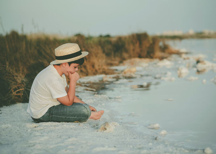 Side view of boy sitting at beach