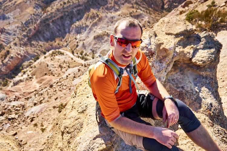 Man wearing sunglasses on rock