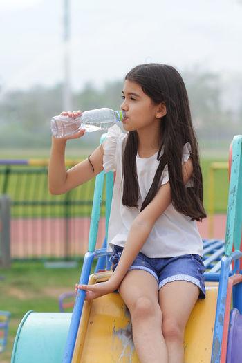Girl drinking water at playground
