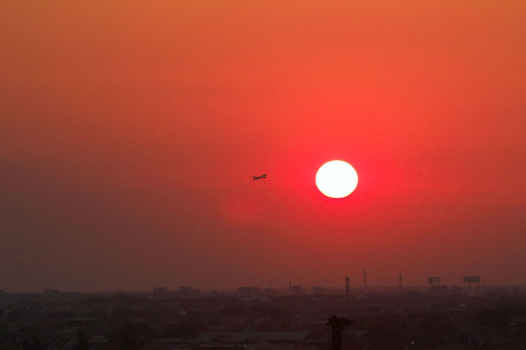 what happen the beauty red sky Air Vehicle Airplane Architecture Building Exterior Built Structure City Day Drone  Flying Mid-air Nature No People Outdoors Parachute Sky Sun Sunset Transportation Flying High Jakarta Indonesia