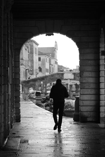 Rear view of silhouette man walking on street amidst buildings