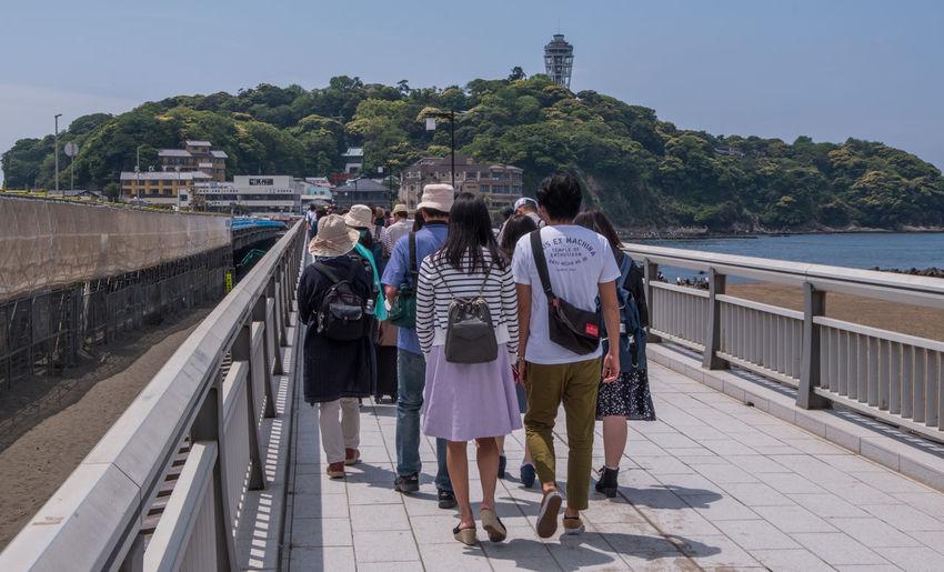Rear view of women walking on bridge