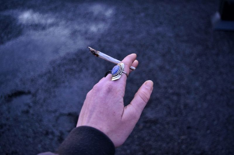 Close-up of hand holding cigarette outdoors