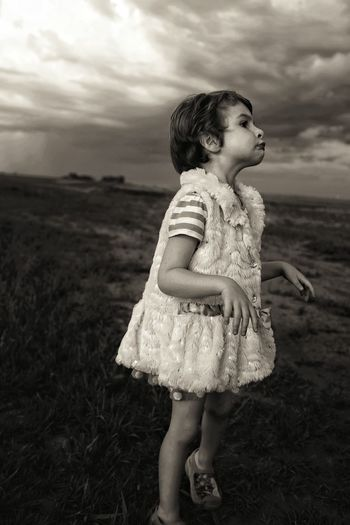 Girl Imitating Zombie On Field Against Cloudy Sky