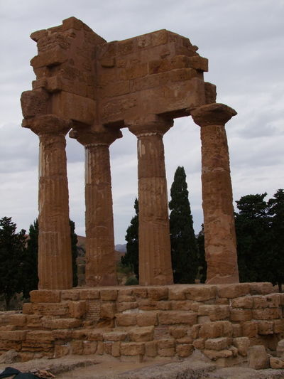 Remains of Temple of Castor and Pollux (5th century BC) Agrigento Ancient Ancient Civilization Architectural Column Architecture Building Exterior Column Composition Famous Place Grey Sky Historic History International Landmark Italy Low Angle View Monument Ruined Sicily Temple Tourism Tourist Attraction  Trees
