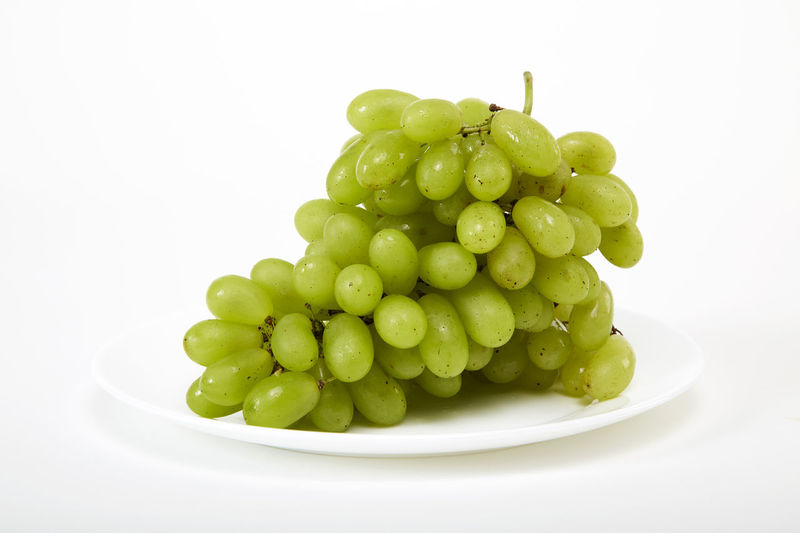Close-up of grapes in bowl over white background
