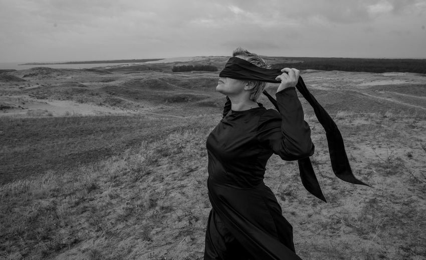 Woman covering eyes with scarf while standing on land