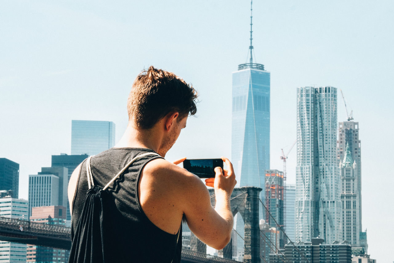 Rear view of man photographing city against clear sky