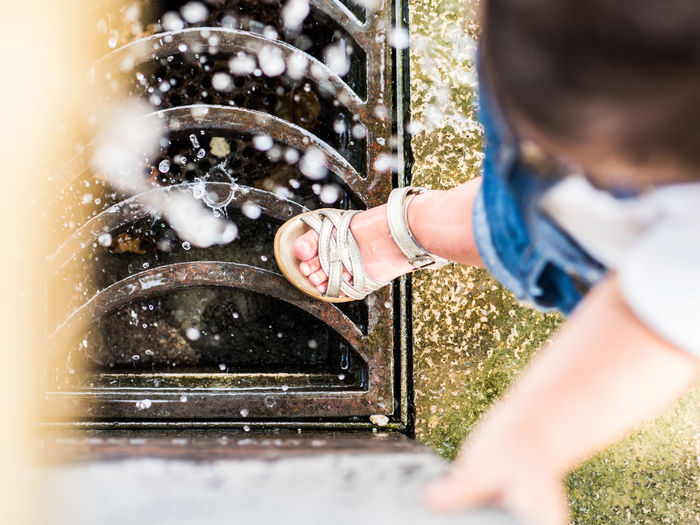 Low angle view of girl playing on fountain