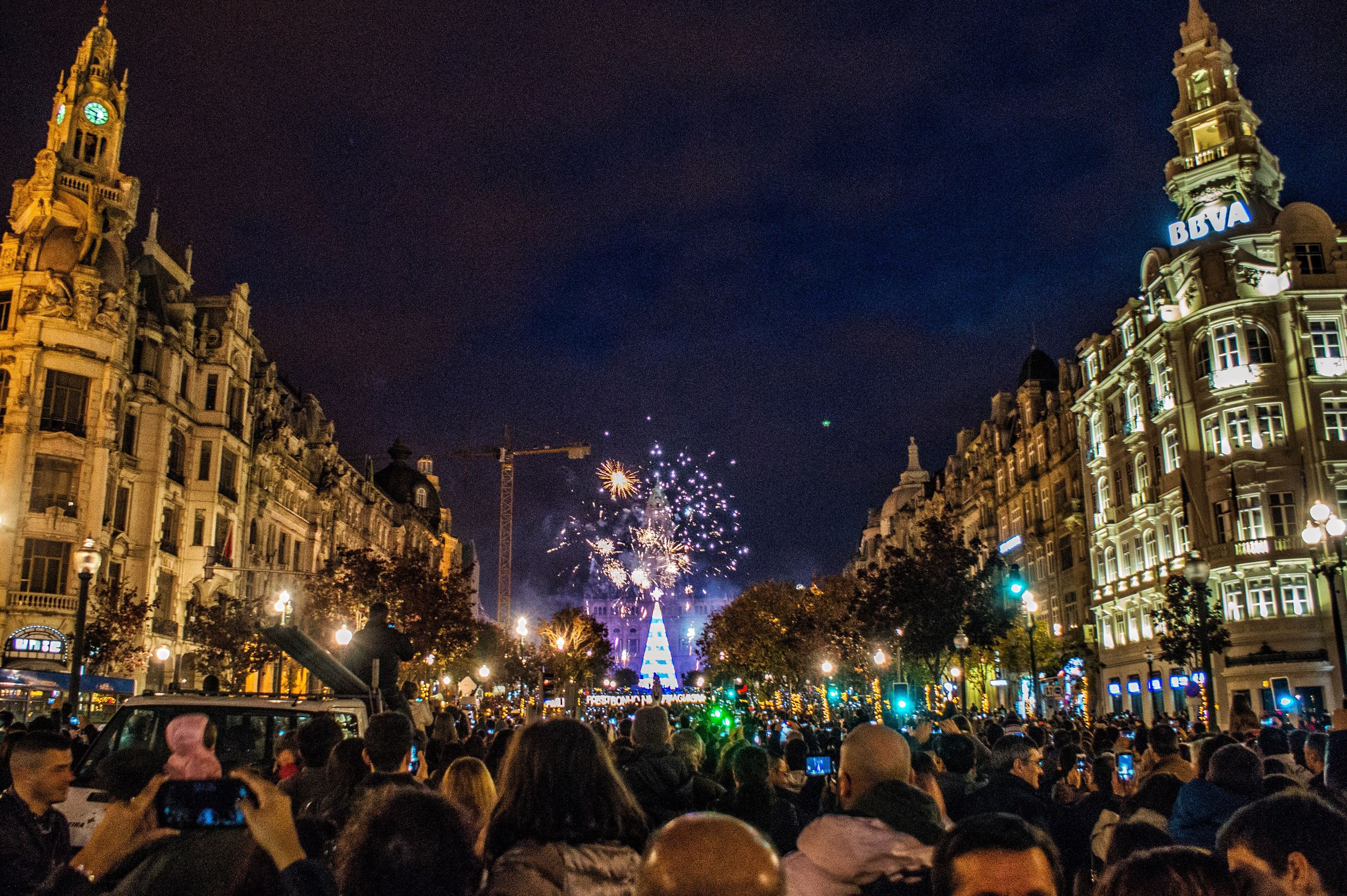 illuminated, night, large group of people, architecture, building exterior, travel destinations, christmas lights, city, christmas, christmas decoration, outdoors, sky, religion, built structure, christmas tree, christmas market, crowd, people
