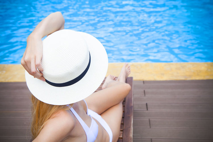 Midsection of woman sitting in swimming pool