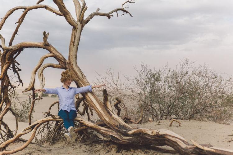 Woman sitting by dead tree