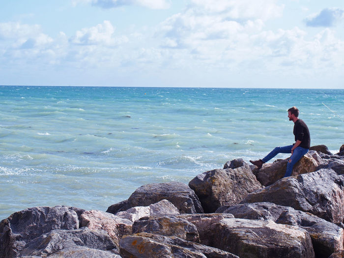 Side View Of Man Looking At Sea While Sitting On Rocks Against Sky
