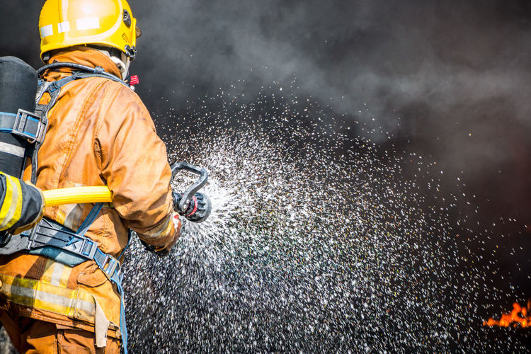 Accidents And Disasters Clothing Fire Hose Firefighter Hose Men Motion Nature Occupation One Person Outdoors Protection Protective Workwear Rain Rescue Worker Smoke - Physical Structure Spraying Uniform Water Wet Working