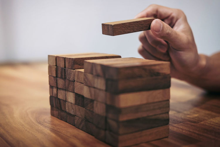 Cropped Image Of Man Stacking Dominoes On Table