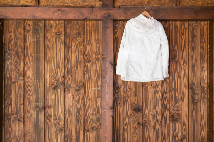 Shirt On Coathanger Against Wooden Wall At Home