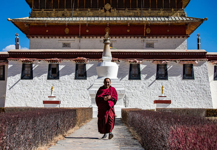 Lama Architecture Belief Religion One Person Building Built Structure Real People Spirituality Place Of Worship Traditional Clothing Building Exterior Front View Clothing Day Adult Nature Outdoors Tibet Travel Tibetan Culture Monk  Lama Temple Walking Tibetan Monk 喇嘛