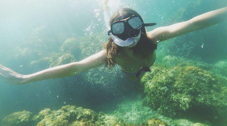 Woman snorkeling by coral undersea