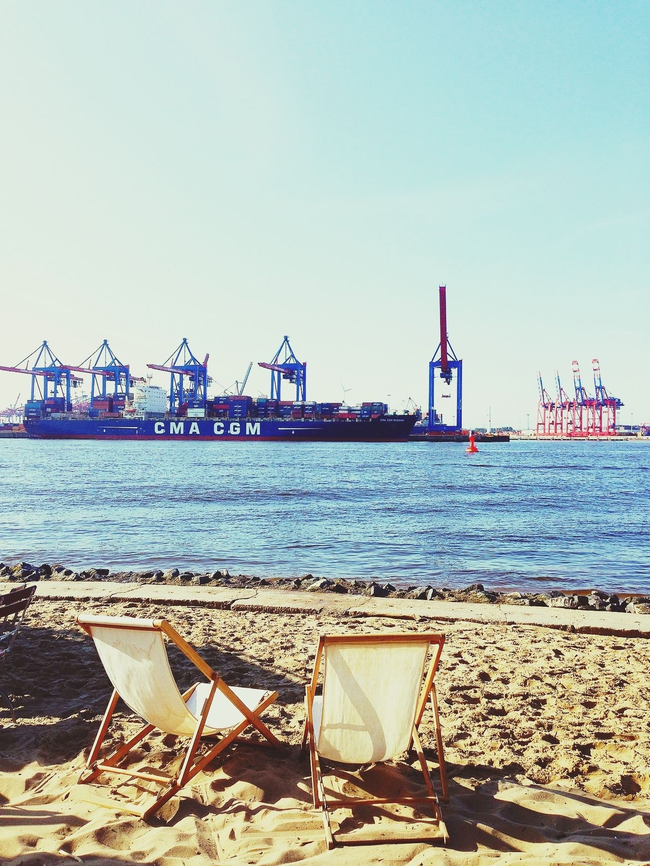 Container ship docked at port with empty deck chairs in foreground