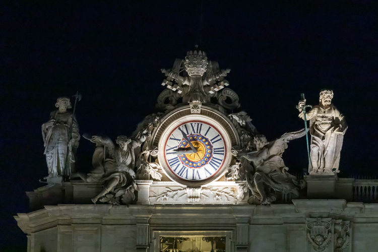 Low angle view of statue of illuminated building at night