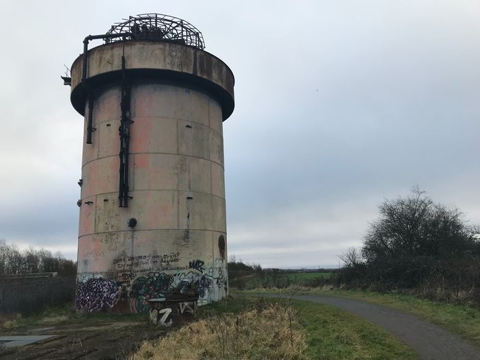 Old water tower Tower Steam Train Railway Steel Tagged Graffiti Field Sky Day Agriculture Outdoors Tree Landscape No People Grass Water Tower - Storage Tank Architecture
