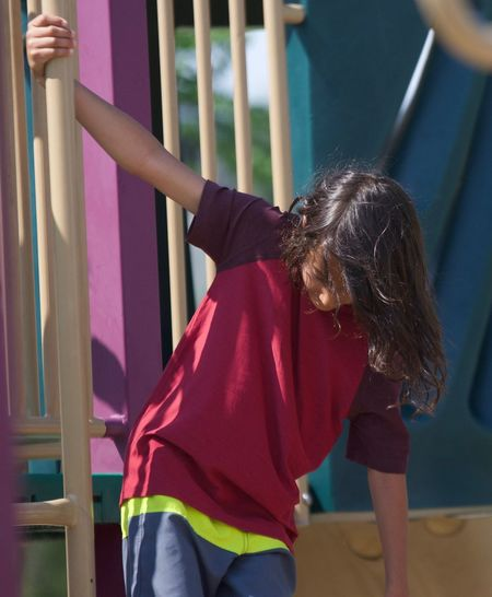 Rear view of girl standing on slide in playground