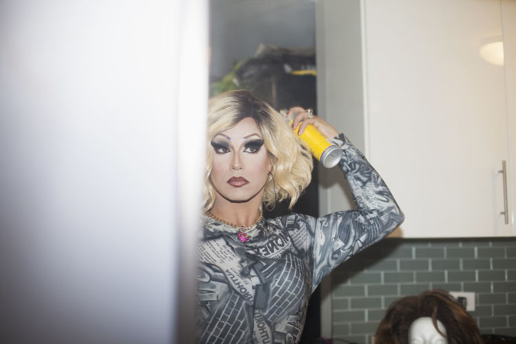 Drag queen spraying hairspray