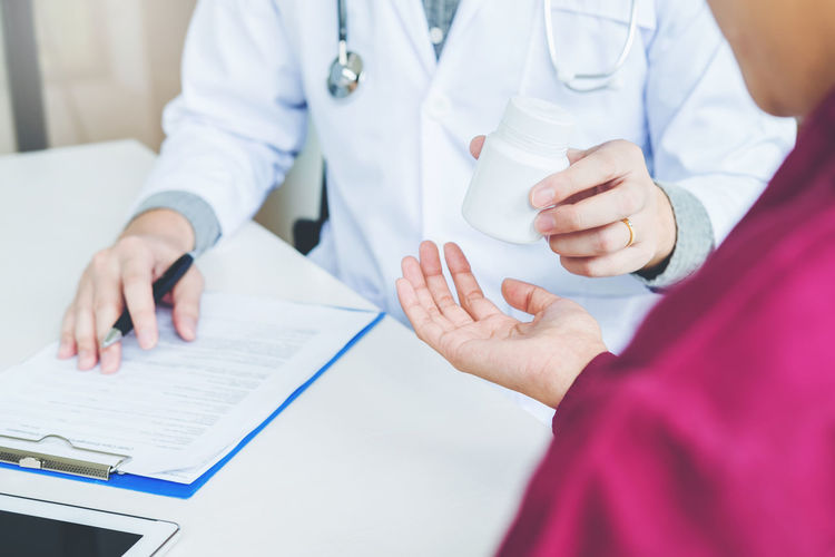 Midsection of doctor discussing with patient on table in hospital