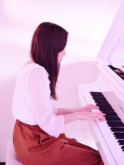 Rear view of woman playing piano